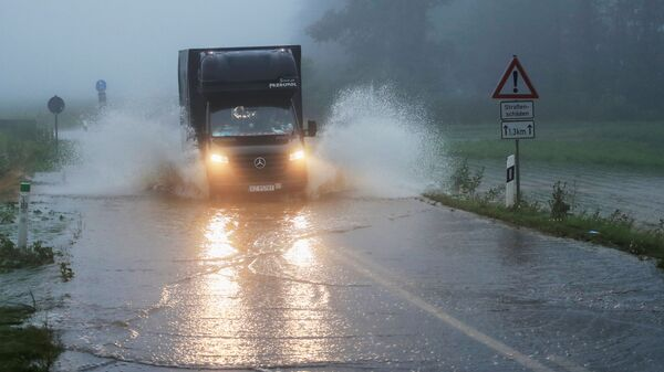Автомобиль едет по дороге, пострадавшей от наводнения, Германия - Sputnik Latvija
