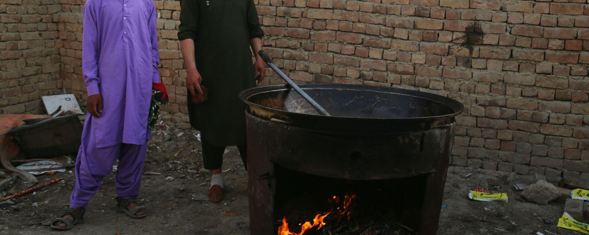 Люди готовят еду во временном лагере для пострадавших в результате боевых действий, на одной из улиц Кабула - Sputnik Латвия, 1920, 20.08.2021