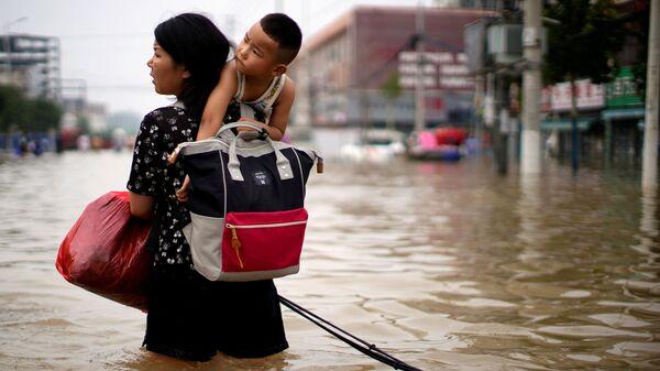 Женщина с ребенком и вещами пробирается через паводковые воды после проливного дождя в Чжэнчжоу, провинция Хэнань, Китай - Sputnik Латвия