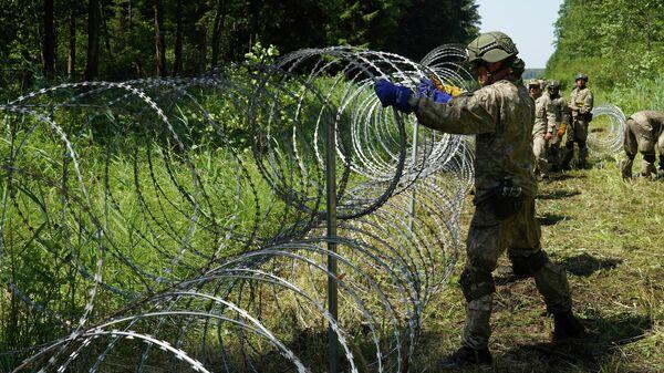 Литовские военнослужащие устанавливают колючую проволоку на границе с Беларусью в Друскининкае - Sputnik Латвия