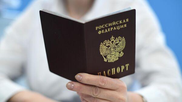 Сотрудник ПФР держит в руках паспорт РФ - Sputnik Латвия