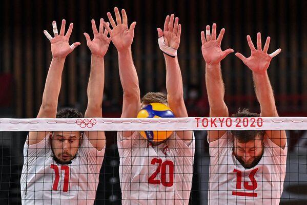 Poļu volejbolisti Fabiāns Držizga, Mateušs Benieks un Mijails Kubjaks pūlas bloķēt sitienu mačā ar Venecuēlu - Sputnik Latvija
