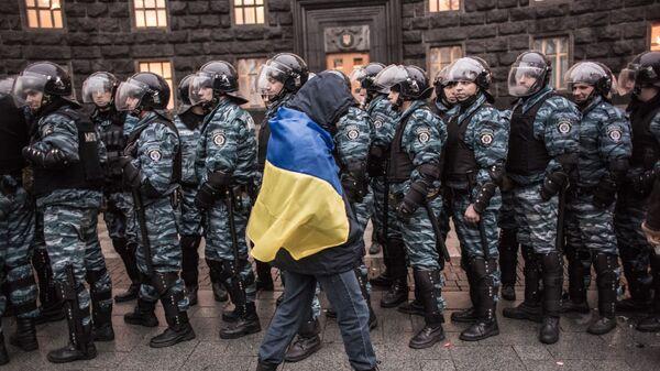 Сторонник евроинтеграции Украины и сотрудники милиции у здания правительства страны в Киеве - Sputnik Latvija