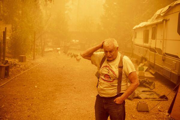 Местный житель во время пожаров в штате Калифорния, США - Sputnik Латвия