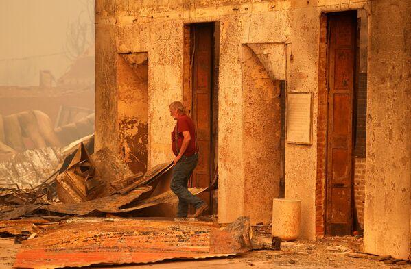 Житель осматривает сгоревшее коммерческое здание, принадлежащее его другу, после пожара, разразившегося в городе Гринвилл, штат Калифорния - Sputnik Латвия