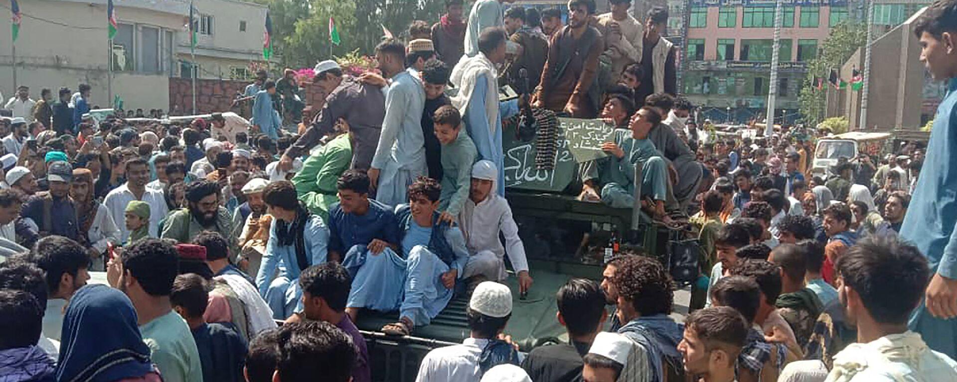 Боевики Талибан* и местные жители на армейском вседорожнике афганской армии в Джелалабаде - Sputnik Latvija, 1920, 01.09.2021