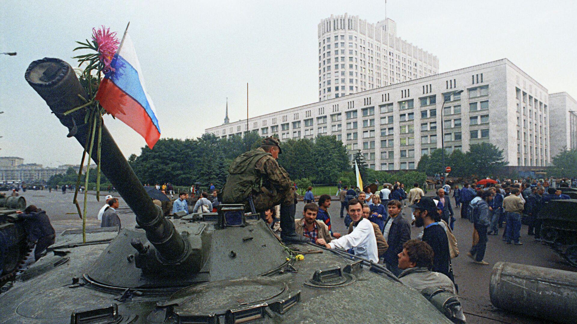 Защитники Белого дома прикрепили цветы к орудийному стволу одного из танков, введенных в Москву 19 августа 1991 года в связи с объявлением членами ГКЧП чрезвычайного положения в столице - Sputnik Латвия, 1920, 19.08.2021