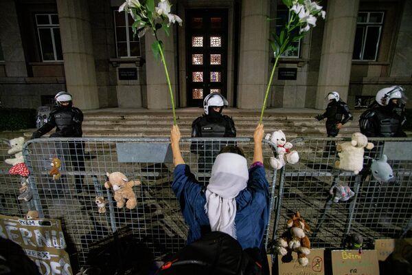 Женщина пришла на митинг с цветами, которыми размахивала у забора с выстроившимися полицейскими - Sputnik Латвия