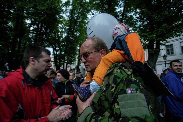 Мужчина пришел на митинг с куклой ребенка, выступая против обязательной вакцинации детей - Sputnik Латвия
