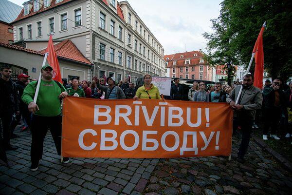 Участники митинга пришли на акцию с плакатами, требуя свободы выбора в вопросе вакцинации против COVID-19 - Sputnik Латвия