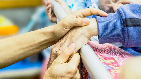Социальный работник держит за руку пожилого человека - Sputnik Латвия