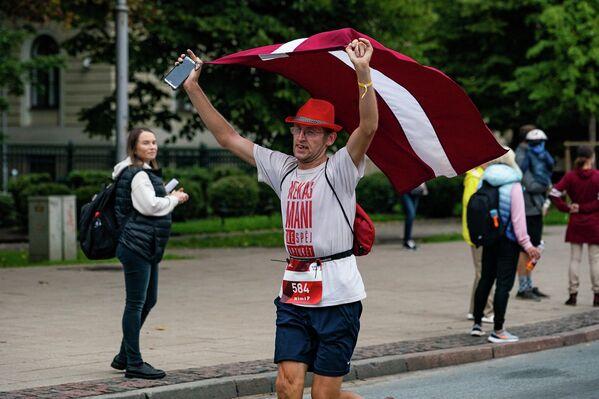 Участник Рижского марафона пробежал всю дистанцию с латвийским флагом - Sputnik Латвия