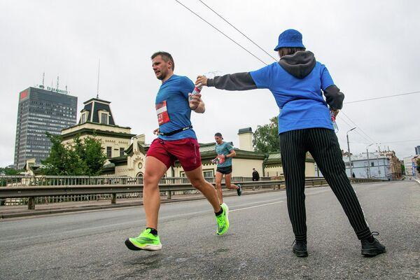 Спортсмен берет бутылку воды на дистанции марафона - Sputnik Латвия