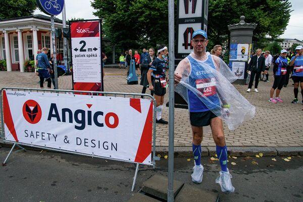 Спортсмен разминается перед стартом Рижского марафона - Sputnik Латвия