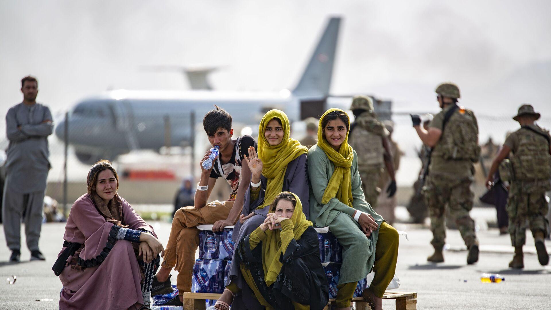 Женщины и дети в ожидании эвакуации в аэропорту Кабула  - Sputnik Латвия, 1920, 07.09.2021