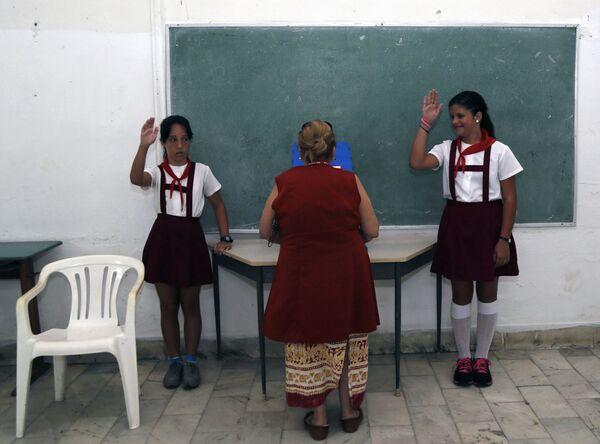 Школьники приветствуют женщину, голосующую во время первых местных выборов на Кубе. - Sputnik Латвия