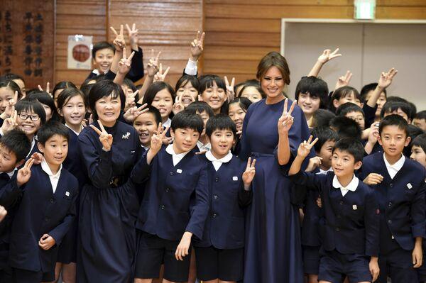 Бывшая первая леди США Мелания Трамп и Акиэ Абэ, супруга японского премьер-министра Синдзо Абэ,  фотографируются со школьниками в начальной школе Kyobashi Tsukiji в Токио. - Sputnik Латвия
