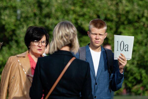 Старшеклассник держит табличку с названием своего класса - Sputnik Латвия