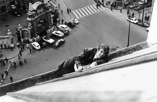 """В юности Бельмондо пришлось пожертвовать спортивной карьерой ради актерского ремесла, но хорошая физическая форма стала отличным подспорьем в кинокарьере артиста. На фото: Бельмондо на парижской крыше во время съемок фильма """"Страх над городом"""", 1975. - Sputnik Латвия"""