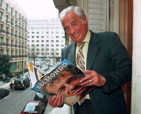 Кинокарьеру Бельмондо называют одной из самых коммерчески успешных во Франции. На фото: Бельмондо с книгой о себе, 1996. - Sputnik Латвия