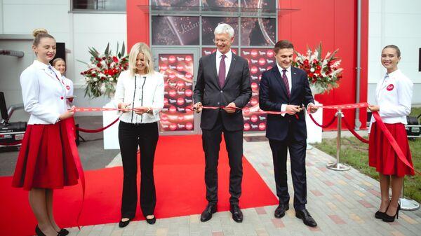 Премьер-министр Латвии Кришьянис Кариньш(в центре) перерезает ленточку на церемонии открытия фабрики Laima в Адажи - Sputnik Latvija