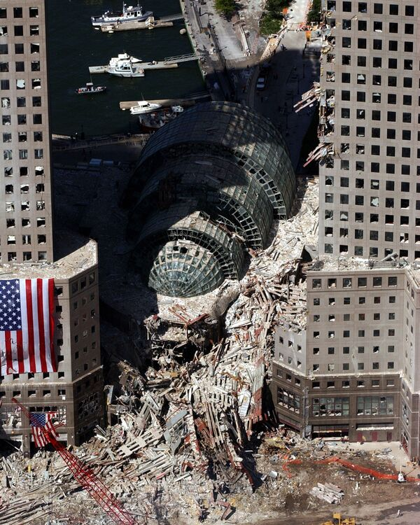 Вид с воздуха на рухнувший Всемирный торговый центр. Окружающие здания были сильно повреждены обломками и мощным ударом падающих башен-близнецов.На борту четырех самолетов находились в сумме 246 пассажиров и членов экипажа. Все погибли, в том числе 19 угонщиков-камикадзе. - Sputnik Латвия
