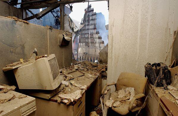 Из офиса, заполненного пылью и обломками, виден обрушившийся небосреб башен-близнецов.  - Sputnik Латвия