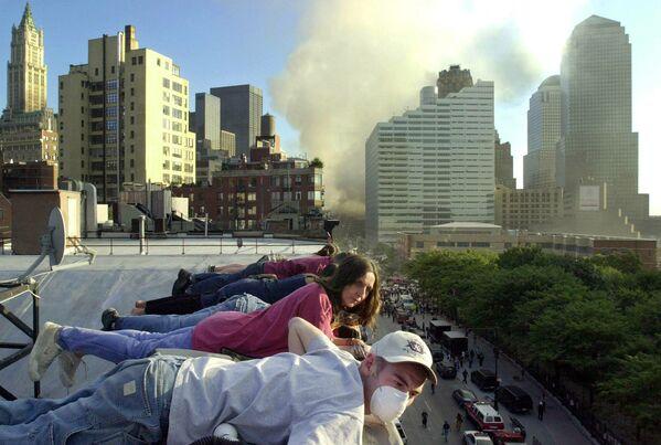 Жители наблюдают с крыши здания на Гринвич-стрит в Нью-Йорке за спасательными работами внизу. - Sputnik Латвия