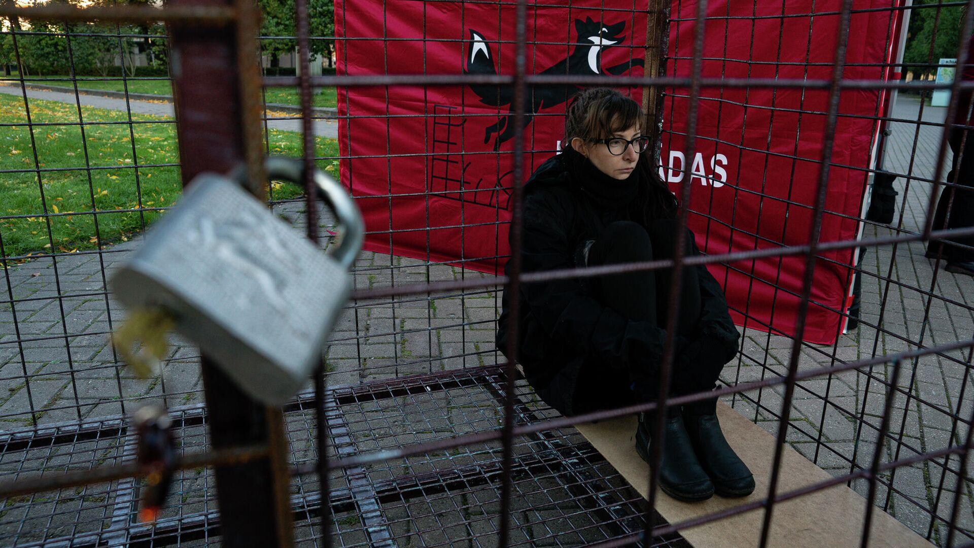 Волонтер Валерия сидит в клетке, протестуя против пушного звероводства в Латвии - Sputnik Латвия, 1920, 16.09.2021