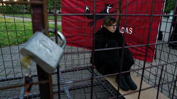 Волонтер Валерия сидит в клетке, протестуя против пушного звероводства в Латвии - Sputnik Латвия