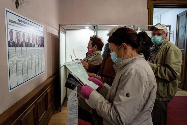 Люди внимательно изучают информацию о выборах. - Sputnik Латвия