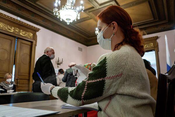 Члены избирательной комиссии в масках и перчатках. - Sputnik Латвия