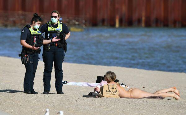 Policisti sarunājas ar meiteni, kas atpūšas pludmalē Melburnā - Sputnik Latvija