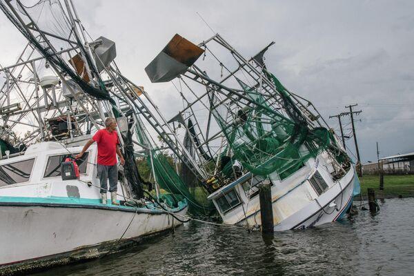 """Luiziānas iedzīvotājs pie laivas, ko daļēji nogremdējis orkāns """"Ida"""" - Sputnik Latvija"""