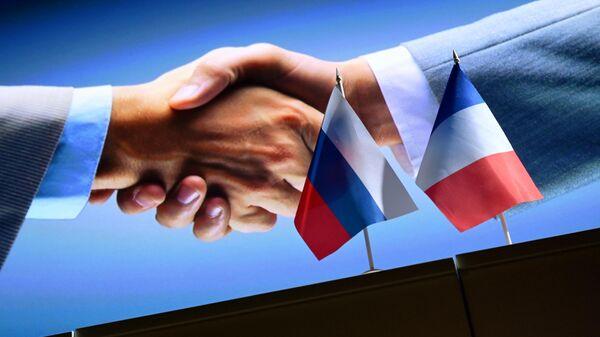 Рукопожатие на фоне государственных флагов России и Франции - Sputnik Латвия