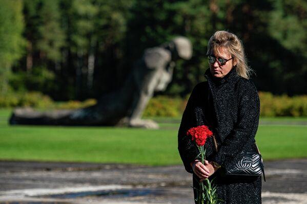 Sieviete ar ziediem Salaspils koncentrācijas nometnes atbrīvošanas 77. gadadienai veltītajā ceremonijā - Sputnik Latvija