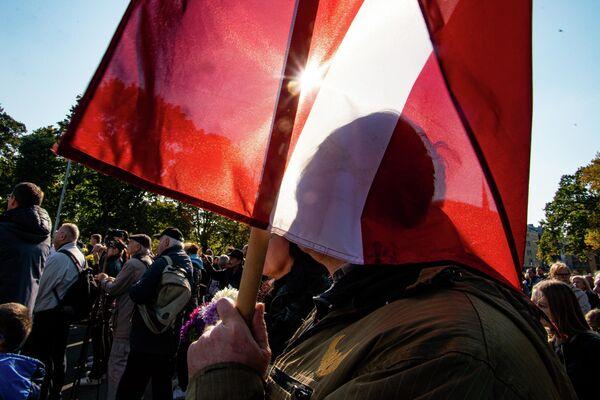 Мужчина с флагом Латвии на митинге протеста у памятника Свободы - Sputnik Латвия