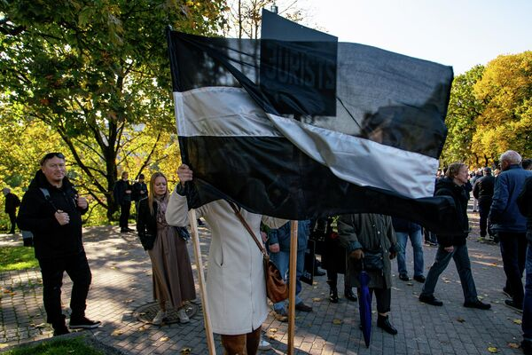 Латвийский флаг в черно-белом исполнении на митинге протеста - Sputnik Латвия