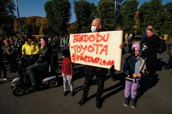 """Мужчина с плакатом """"Продаю Toyota"""" на митинге протеста у памятника Свободы - Sputnik Латвия"""