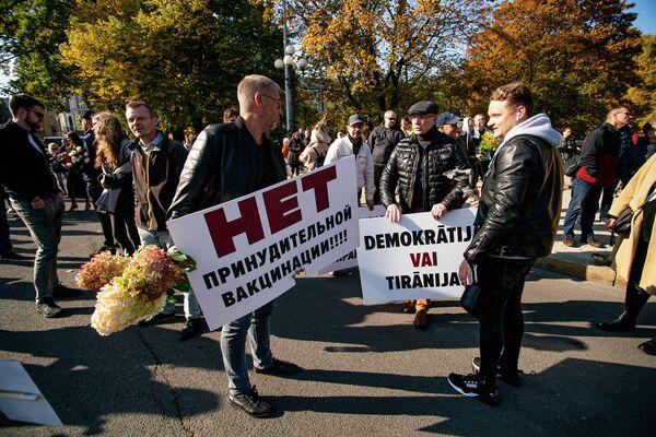 Мужчины с плакатами на митинге протеста - Sputnik Латвия