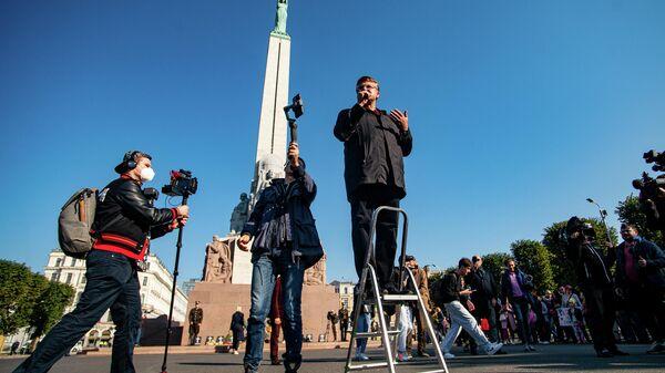 Латвийский оппозиционный политик Айнарс Шлесерс обратился к собравшимся со стремянки - Sputnik Латвия