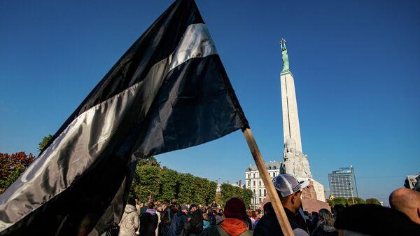 Латвийский флаг в черно-белом исполнении на митинге протеста у памятника Свободы - Sputnik Латвия