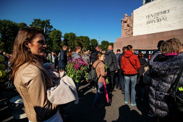 Женщина с грудным ребенком на митинге протеста у памятника Свободы - Sputnik Латвия