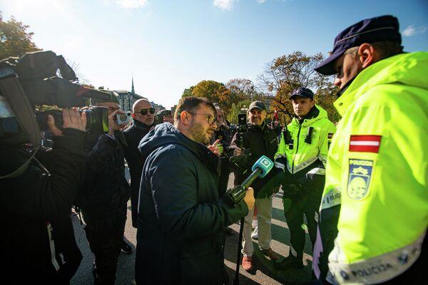 Latvijas televīzijas žurnālists Aleksejs Dunda lūdz policijas darbiniekus aizsargāt viņu un operatoru no uzmācīgiem protestētājiem - Sputnik Latvija