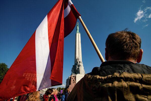 Vīrietis ar Latvijas karogu protesta akcijā pie Brīvības pieminekļa - Sputnik Latvija