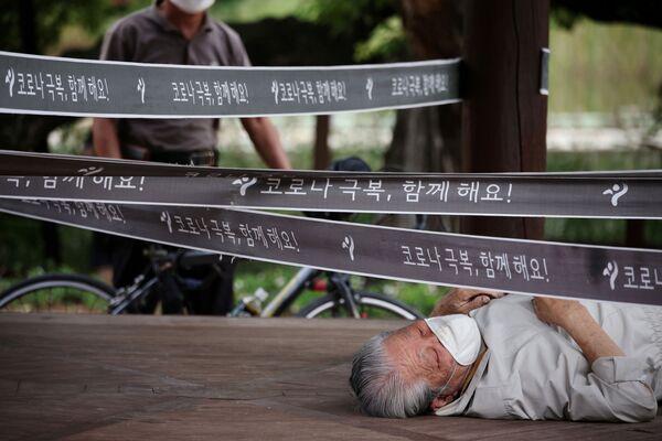 Vīrietis pie paviljona, kas ielenkts Covid-19 izplatības novēršanai Seulas parkā - Sputnik Latvija