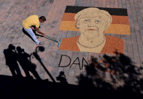 Kosovo mākslinieks Alkents Požegu strādā pie Vācijas kancleres Angelas Merkeles portreta, ko izveidojis no graudiem un sēklām - Sputnik Latvija