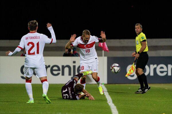 Защитник сборной Турции Джанер Эркин нарушает правила против Алвиса Яунземса - Sputnik Латвия