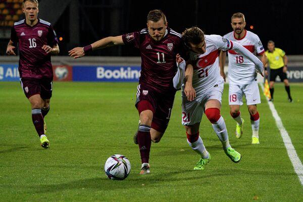 Робертс Савалниекс (слева) ведет борьбу за мяч с Керемом Актюркоглу - Sputnik Латвия