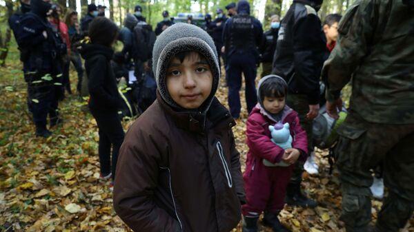 Иракский ребенок в окружении пограничников и полицейских после пересечения белорусско-польской границы в городе Хайнувка, Польша - Sputnik Латвия